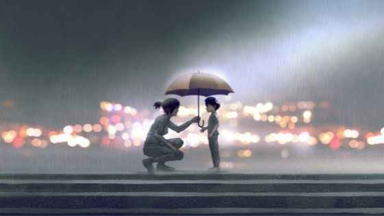 Woman squatting in the rain to hold her umbrella over a small, lost boy
