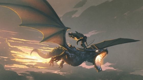 Rider on the back of a dragon flying at sunset