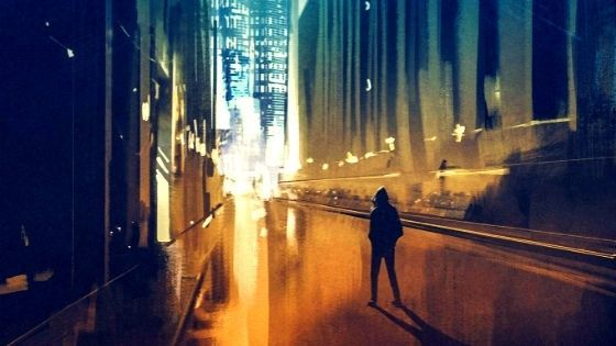 Man standing in an alley with night lights from the city ahead of him
